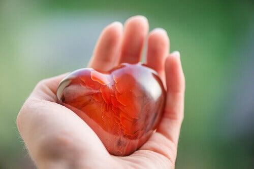 Rotes Herz aus Glas liegt in einer Hand