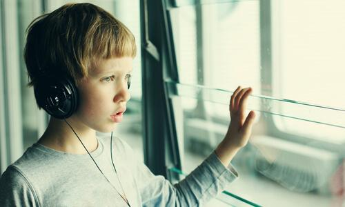 Autistischer Junge hört Musik und schaut aus dem Fenster