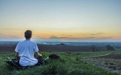 Junge meditiert vor dem Sonnenaufgang