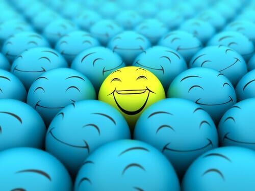 Ein gelber lachender Ball inmitten vieler blauer grinsender Bälle