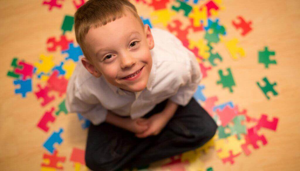 Lachender Junge mit Autismus umgeben von Puzzleteilen
