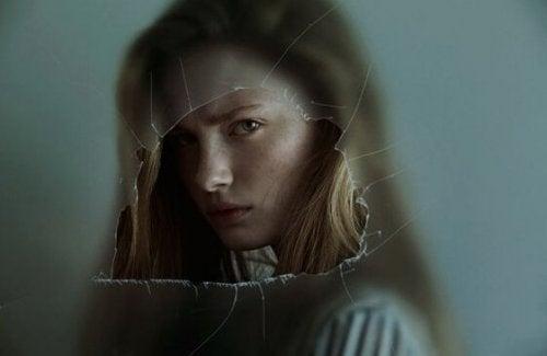 Mädchen hinter einer zerbrochenen Glasscheibe