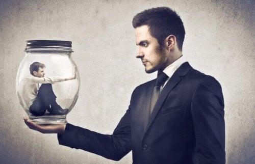 Mann hält anderen Mann im Inneren eines Glases