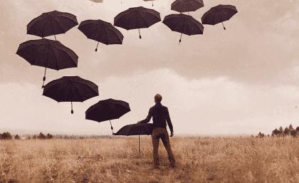 Mann mit Regenschirmen auf einem Feld
