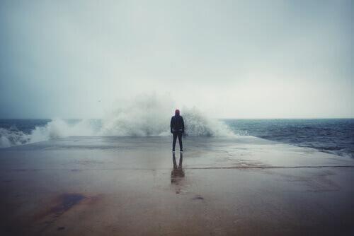 Mann steht vor einem unruhigen Meer