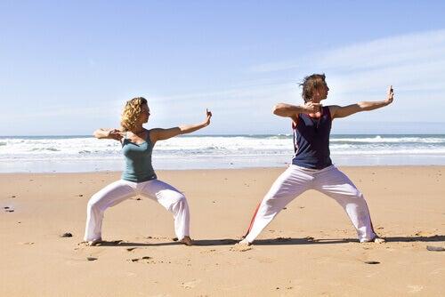 Frau und Mann praktizieren ChiKung am Strand