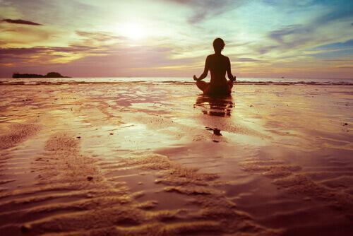 Meditierende Frau am Strand