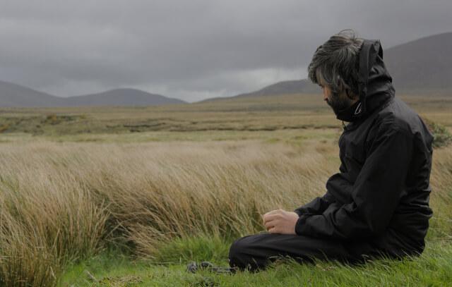 Nachdenklicher Mann sitzt im Gras