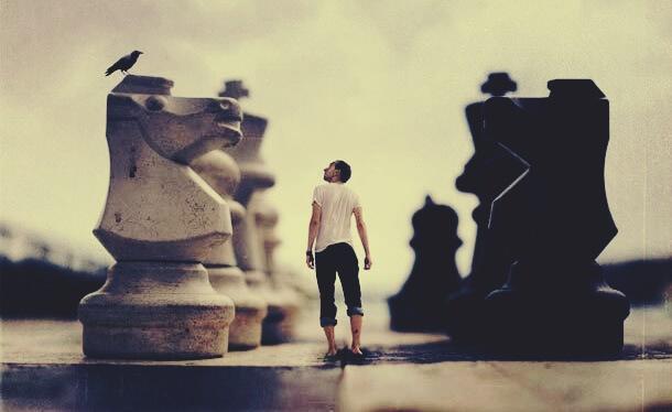 Mann steht auf einem Schachbrett neben Schachfiguren