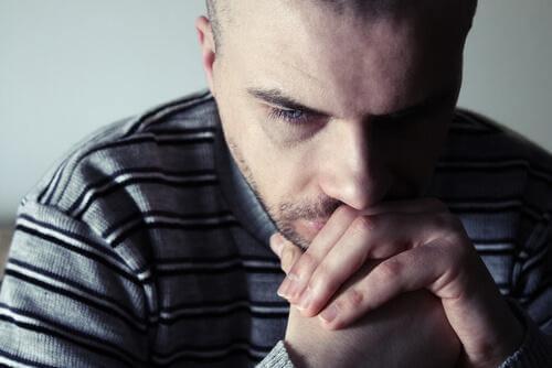 Trauriger Mann lehnt sich auf seine Hände