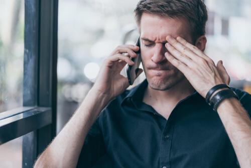 Zorniger Mann telefoniert mit seinem Handy