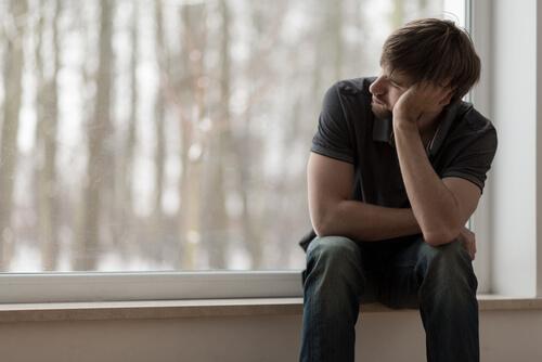 Mann sitzt verzweifelt am Fenster