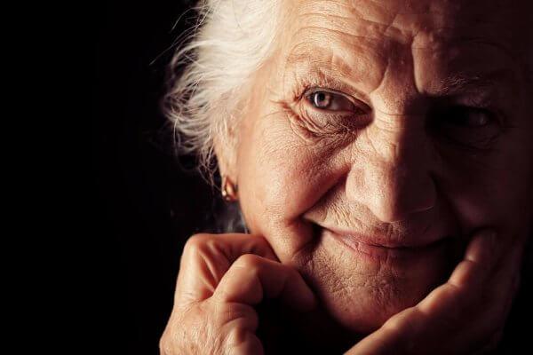 Eine ältere Frau lächelt in eine Kamera.