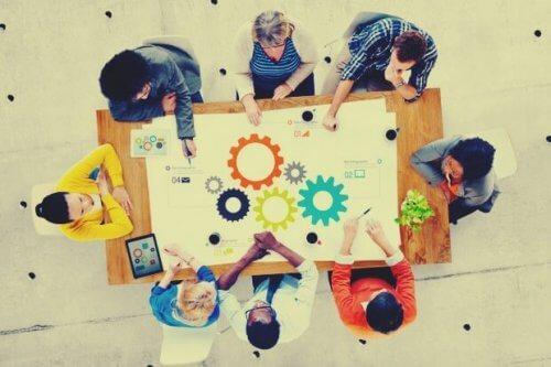Mehrere Mitarbeiter sitzen an einem Tisch und tauschen Ideen aus.