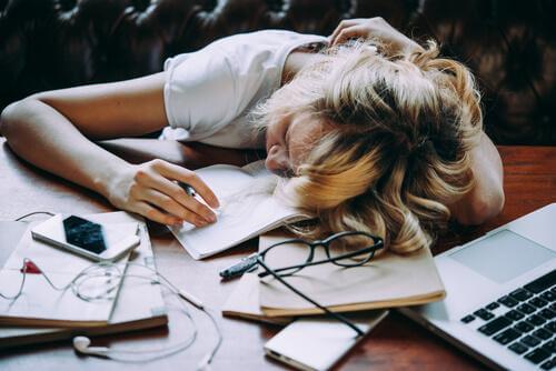 Erschöpfte Frau an ihrem Schreibtisch