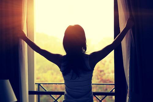 Eine Frau zieht ihre Fenstervorhänge zur Seite, um den Morgen zu begrüßen.