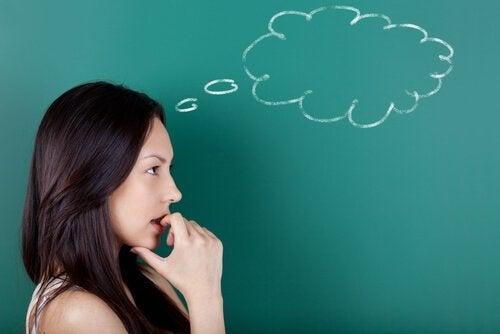 Eine Frau denkt vor dem Hintergrund einer Tafel nach und auf der Tafel sieht man eine leere Gedankenblase.