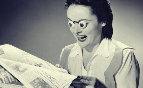 Frau mit falschen Augen liest eine Zeitung