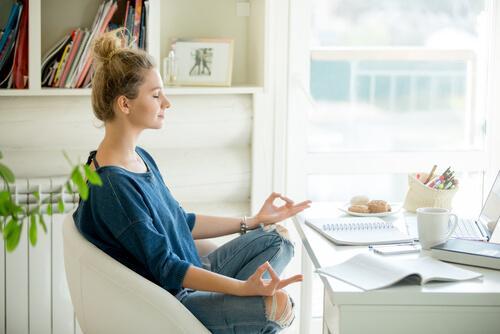 Frau meditiert auf einem Stuhl an ihrem Schreibtisch