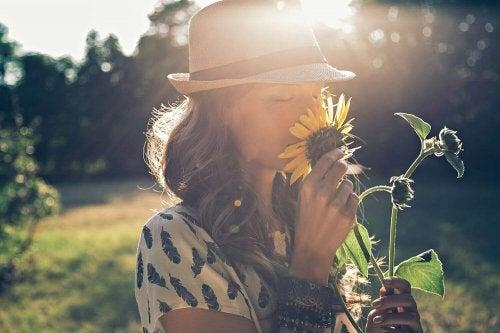 Frau riecht an einer Sonnenblume