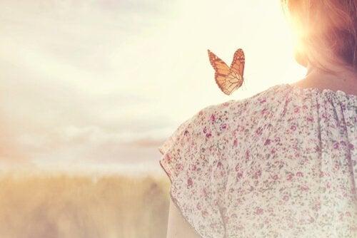 Frau mit einem Schmetterling auf der Schulter