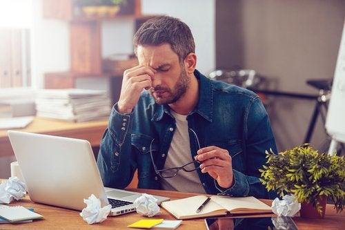 Ein junger Mann sitzt gestresst vor seinem Laptop.
