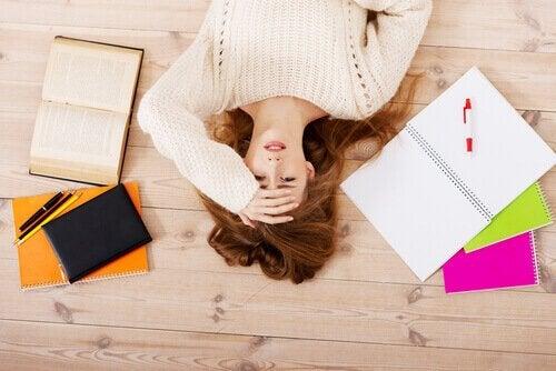 Eine Frau liegt gestresst auf dem Boden und verkörpert den perfektionistischen Prokrastinationstyp.