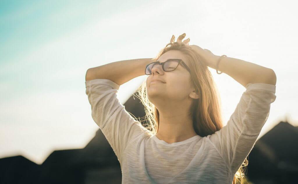 Glückliche Frau mit Brille genießt die Sonne im Gesicht