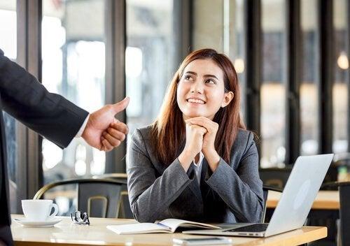 Eine Mitarbeiterin erhält positives Feedback und freut sich.