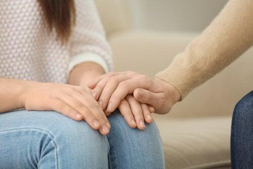 Eine Hand liegt auf einer anderen Hand und spendet Trost.