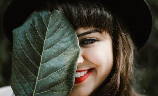 Lachende Frau hält sich ein Blatt vors Gesicht