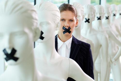 Frau im Anzug zwischen Puppen; allen ist der Mund zugeklebt
