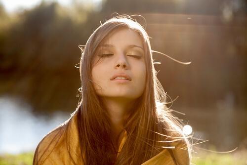 Ein Mädchen genießt die Sonnenstrahlen in seinem Gesicht.