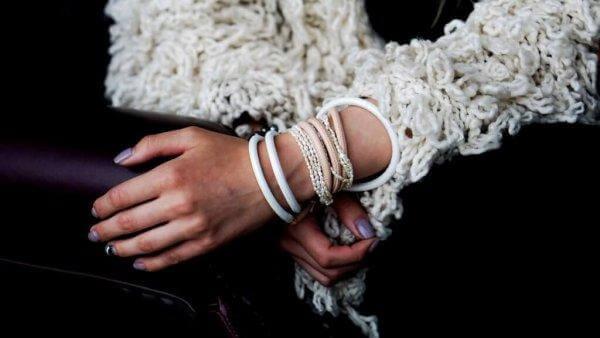 Ein Mädchen trägt einige Armbänder ums Handgelenk.