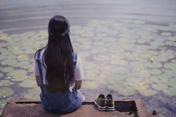 Ein Mädchen sitzt auf einem Steg am Seerosenteich.