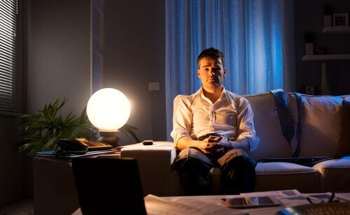 Mann sitzt nachdenklich im Dunkeln