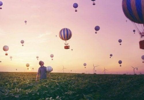 Ein Mann steht in einem Feld und beobachtet Heißluftballons.