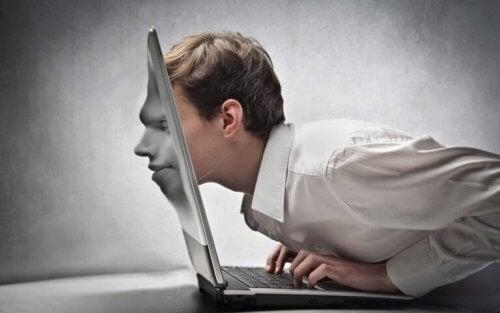 Ein Mann wird in den Bildschirm seines Laptops hineingezogen.
