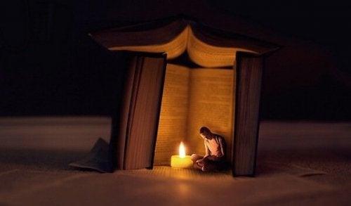 Ein Mann sitzt in der Dunkelheit in einem Zelt aus Büchern vor einer Kerze.