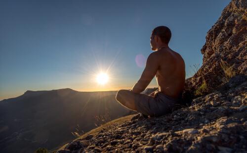Mann meditiert auf einem Berg bei Sonnenaufgang