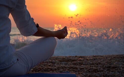 Frau praktiziert Mindfulness am Meer