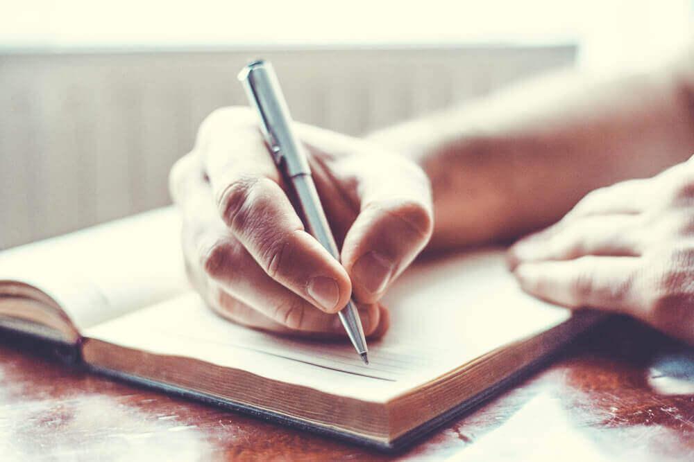 Eine Hand hält einen Stift und scheint Notizen zu machen.