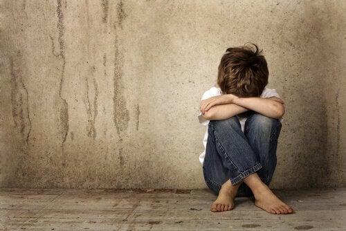 Trauriger Junge sitzt allein auf dem Boden