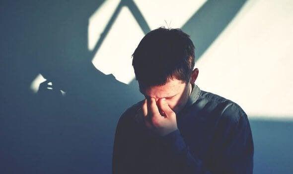Trauriger Mann, der sich eine Hand ins Gesicht hält