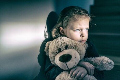 Trauriges Mädchen, das mit einem Teddybär kuschelt