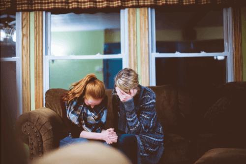Zwei Frauen trauern auf einer Couch