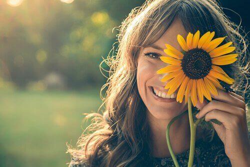 Eine Frau hält sich eine Sonnenblume vors Gesicht.