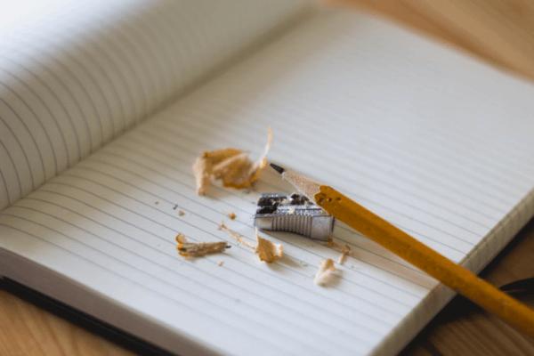 Ein angespitzter Bleistift liegt auf einem aufgeschlagenen Notizbuch.