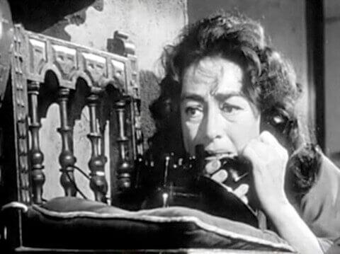 Filmszene aus Baby Jane, die Joan Crawford zeigt, wie sie am Telefon nach Hilfe verlangt