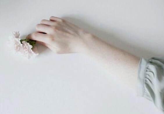 Hand mit pastellfarbenen Blumen